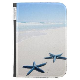 Dos estrellas de mar azules en el borde del agua e