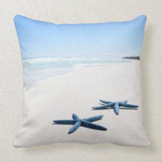 Dos estrellas de mar azules en el borde del agua e almohada