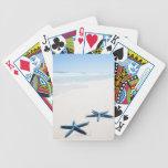 Dos estrellas de mar azules en el borde del agua e barajas de cartas