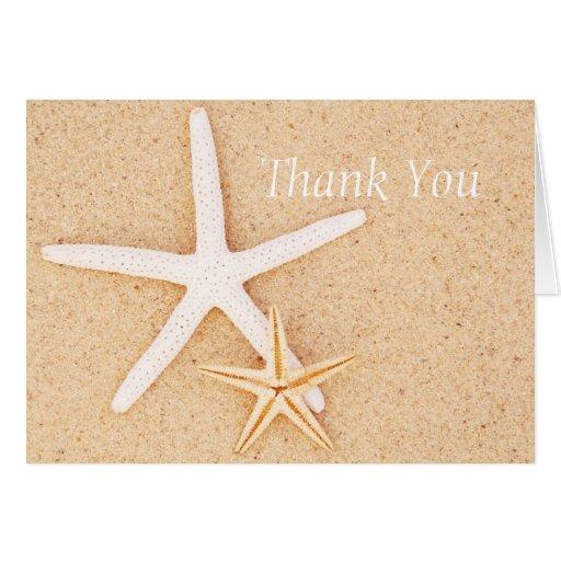Dos estrellas de mar en una playa le agradecen car tarjeta de felicitación