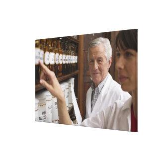 Dos farmacéuticos delante de un estante con latas impresión de lienzo