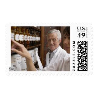 Dos farmacéuticos delante de un estante con latas timbre postal