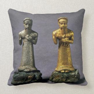 Dos figurillas de los hombres que llevan ofrendas cojín
