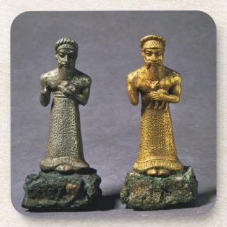 Dos figurillas de los hombres que llevan ofrendas posavasos de bebidas