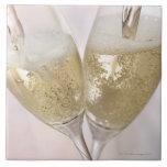 Dos flautas de champán que son llenadas de chispea tejas  ceramicas