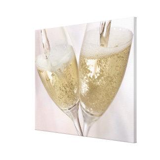 Dos flautas de champán que son llenadas de chispea impresion de lienzo