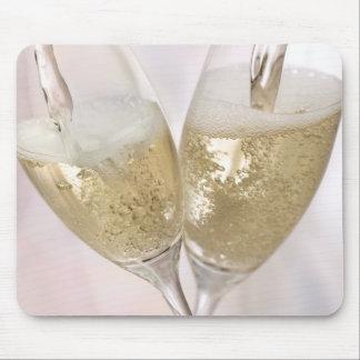 Dos flautas de champán que son llenadas de chispea mouse pads