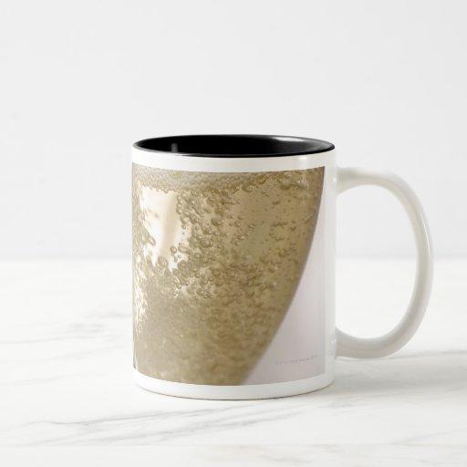 Dos flautas de champán que son llenadas de chispea taza de café
