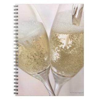Dos flautas de champán que son llenadas de libro de apuntes