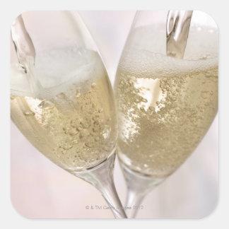 Dos flautas de champán que son llenadas de pegatina cuadrada