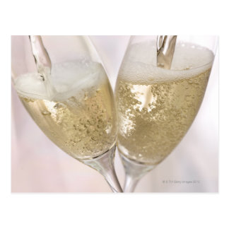 Dos flautas de champán que son llenadas de tarjeta postal