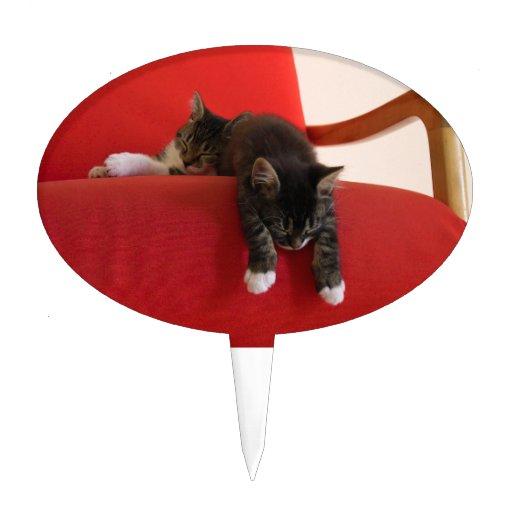Dos gatitos que cuelgan de un amortiguador rojo de figuras para tartas