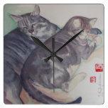 Dos gatos ajustan el reloj de pared
