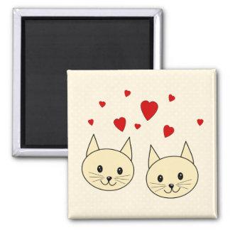 Dos gatos ambarinos lindos del color con los coraz imán cuadrado