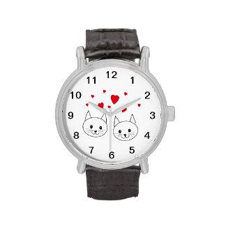 Dos gatos blancos lindos con los corazones rojos relojes