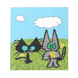 Dos gatos que escogen los dientes de león blocs