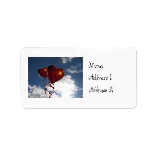 Dos globos del corazón en cielo nublado etiqueta de dirección