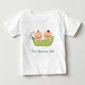 Dos guisantes lindos en gemelos de la vaina de un tshirt