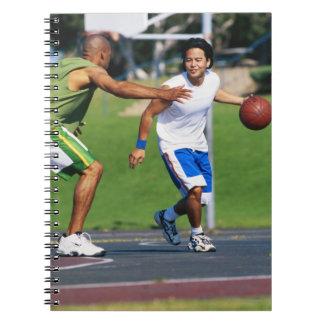 Dos hombres jovenes que juegan a baloncesto libros de apuntes