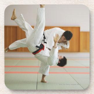 Dos hombres que compiten en un partido 3 del judo posavasos de bebidas