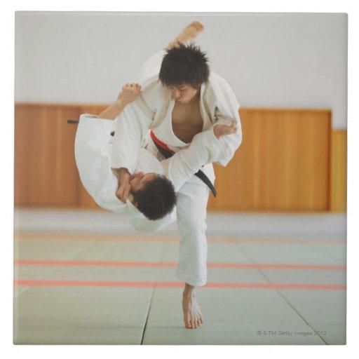 Dos hombres que compiten en un partido del judo azulejo cuadrado grande