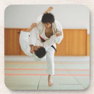 Dos hombres que compiten en un partido del judo posavasos de bebidas