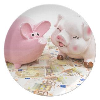 Dos huchas rosadas en notas euro separadas plato de cena