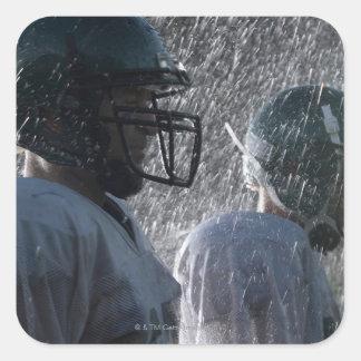 Dos jugadores de fútbol americano en la lluvia, pegatina cuadrada