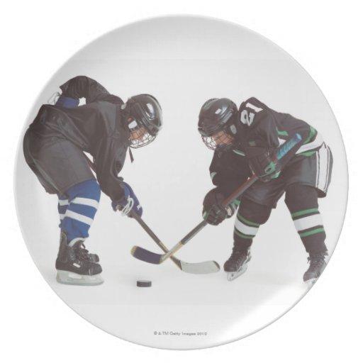 dos jugadores de hockey caucásicos que llevan la o platos