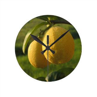 Dos limones maduros que cuelgan en árbol reloj redondo mediano