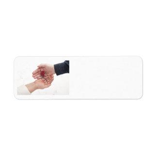 Dos manos con el corazón y las agujas etiqueta de remitente
