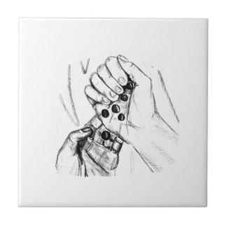 Dos manos con los mármoles que vierten bosquejo de azulejo cuadrado pequeño