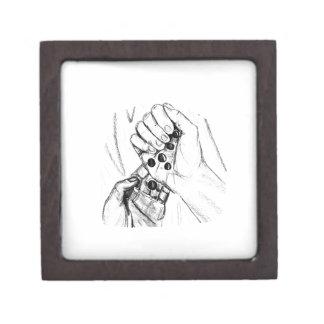 Dos manos con los mármoles que vierten bosquejo de cajas de recuerdo de calidad