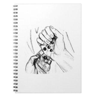 Dos manos con los mármoles que vierten bosquejo de libro de apuntes