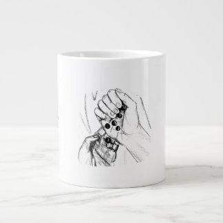 Dos manos con los mármoles que vierten bosquejo de taza grande