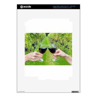 Dos manos que tuestan con las copas de vino en iPad 3 skin