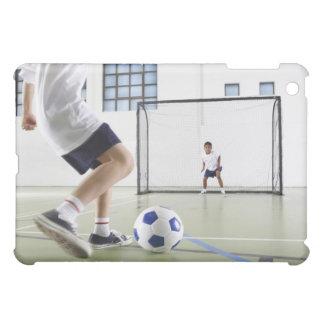Dos muchachos, envejecidos 8-9, jugando a fútbol e