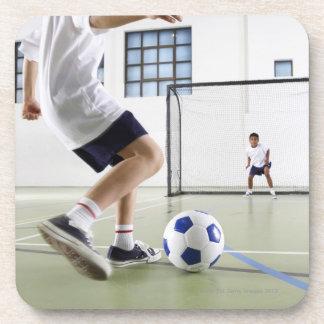Dos muchachos, envejecidos 8-9, jugando a fútbol posavasos