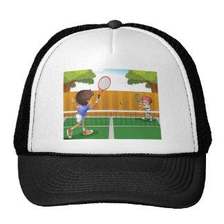 Dos muchachos que juegan a tenis dentro de la gorros bordados
