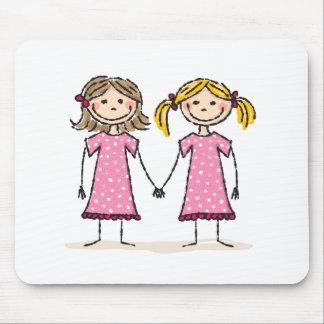 Dos niñas que llevan a cabo las manos alfombrillas de ratones
