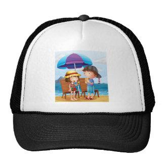 Dos niños en la playa cerca de las sillas de gorras de camionero