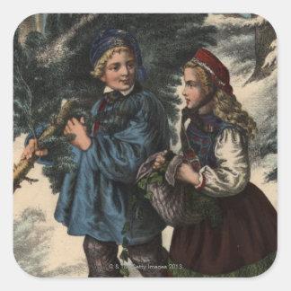 Dos niños que recogen un árbol de navidad y una pegatina cuadrada