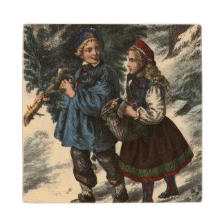 Dos niños que recogen un árbol de navidad y una posavasos de arce