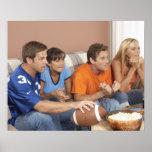 Dos pares que miran fútbol en sala de estar impresiones