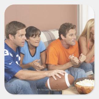 Dos pares que miran fútbol en sala de estar pegatina cuadrada
