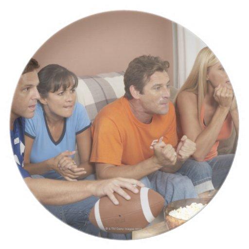 Dos pares que miran fútbol en sala de estar platos