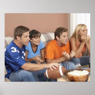 Dos pares que miran fútbol en sala de estar póster