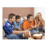 Dos pares que miran fútbol en sala de estar tarjetas postales