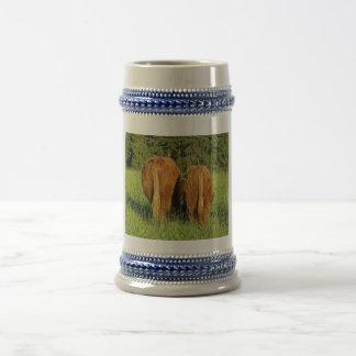 Dos partes posteriores del ganado de la montaña en tazas de café