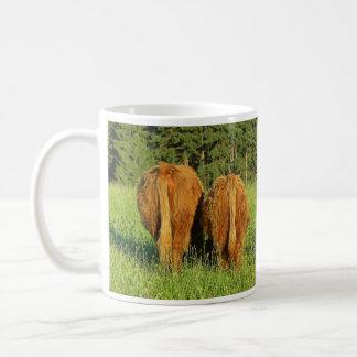 Dos partes posteriores del ganado de la montaña en taza de café